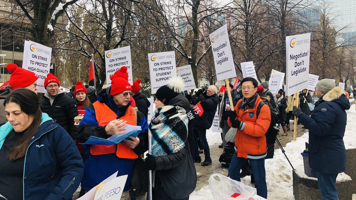 Des manifestants avec des pancartes où l'on peut lire en anglais, «en grève pour protéger une éducation de qualité et les étudiants».