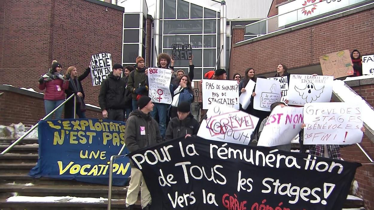 Des étudiants brandissent des affiches devant le Cégep du Vieux-Montréal.