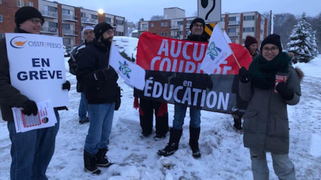 Des grévistes qui tiennent des pancartes et des bannières où il est écrit « En grève » et « Aucune coupure en éducation ».