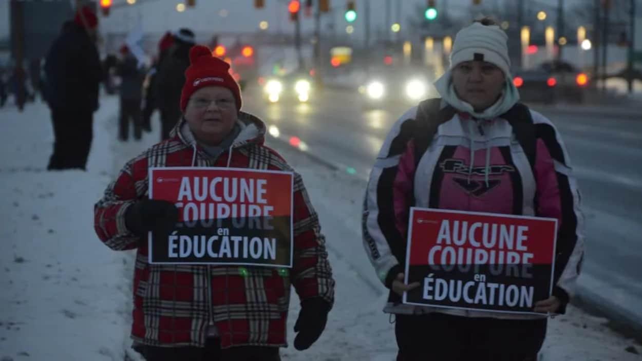 Deux femmes tiennent des pancartes.
