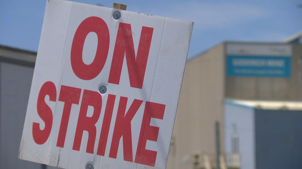Une pancarte sur laquelle on peut lire « En grève » et un édifice industriel en arrière-plan.