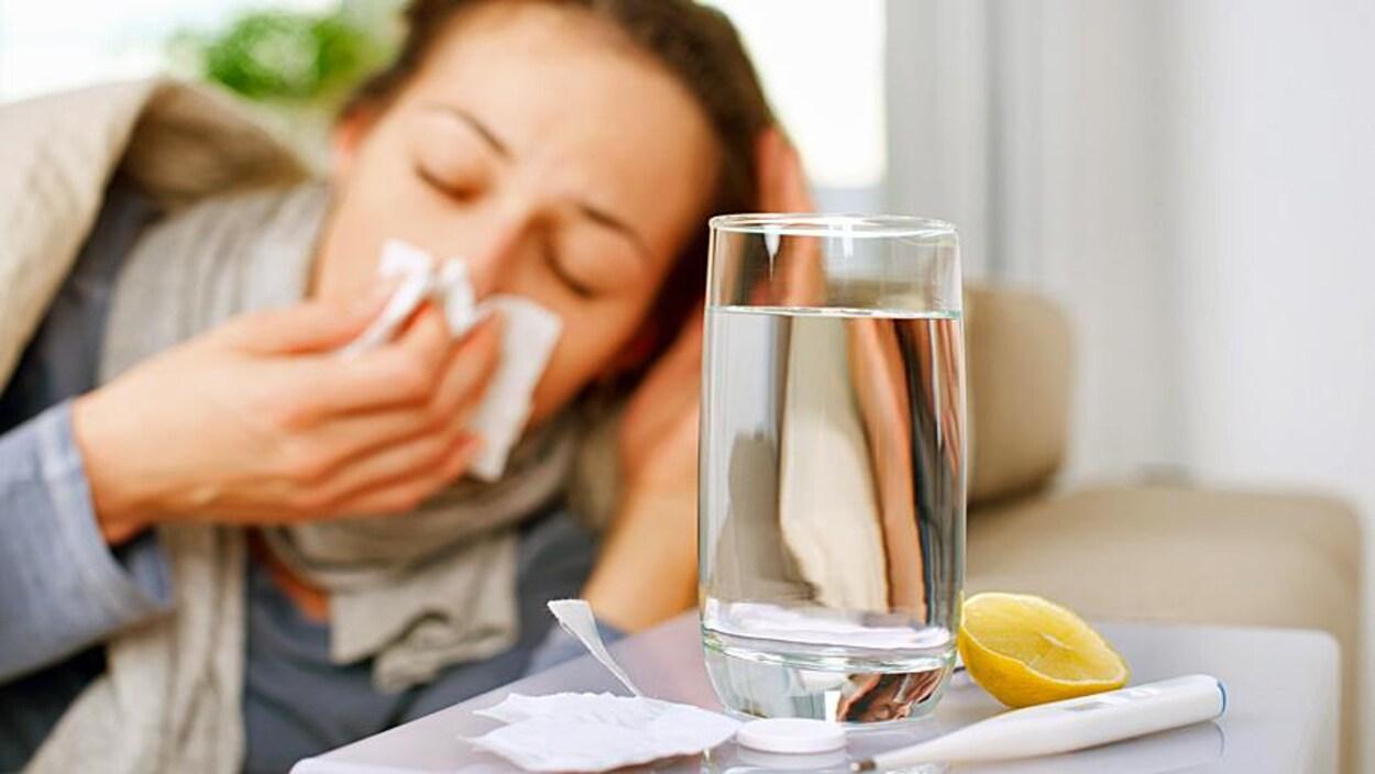 Une femme est couchée près d'un verre d'eau, d'un thermomètre et d'un morceau de citron. Elle semble éternuer dans un mouchoir et est visiblement mal en point.