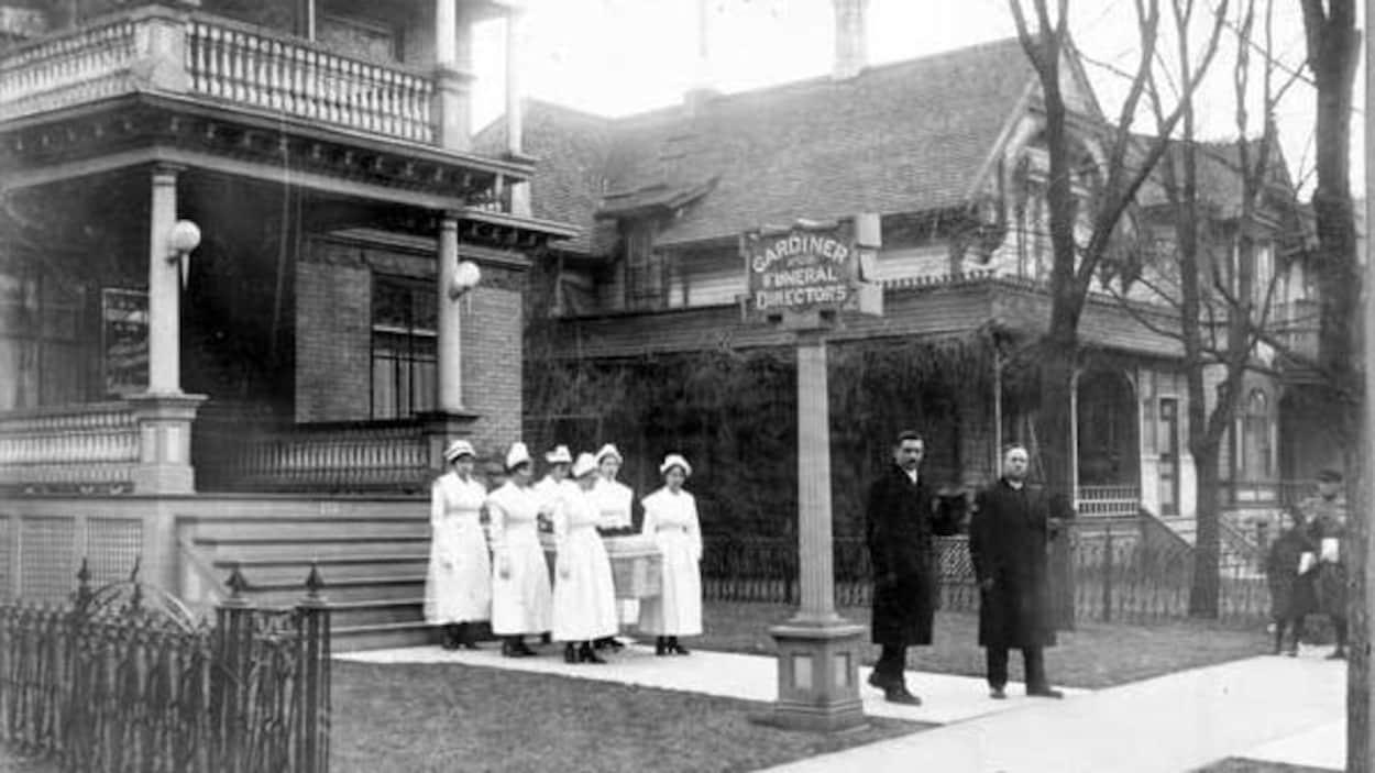 Sur une photo en noir et blanc, on voit six infirmières qui portent un cercueil, sortant d'un bâtiment et devancées par deux hommes habillés de longs manteaux noirs.