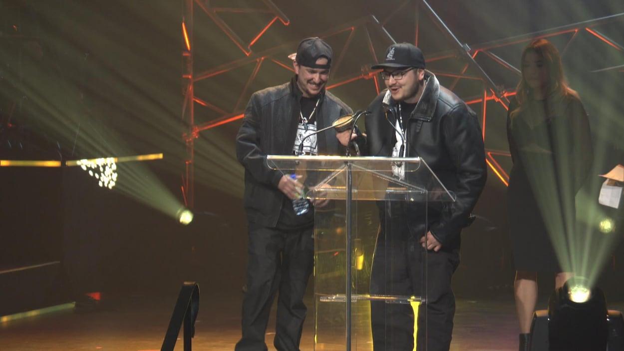 Les deux frères au podium recevant un prix à la salle J.-Antonio-Thompson.