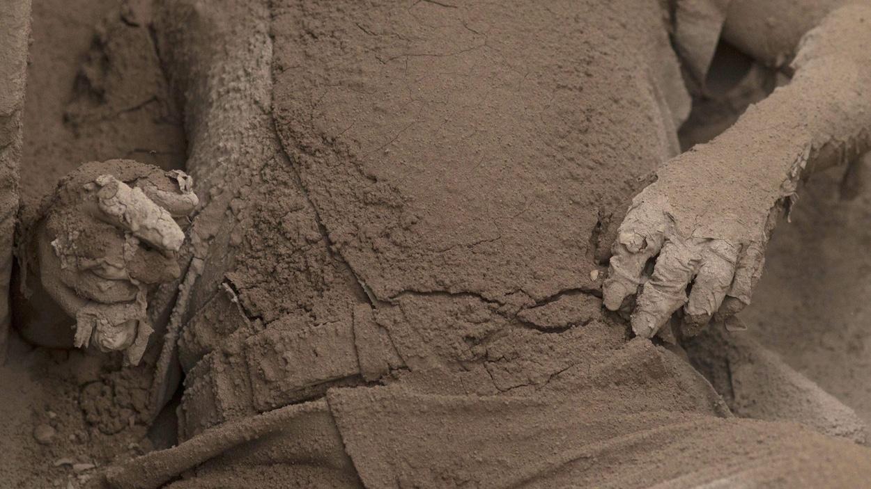 On voit des mains et un torse ensevelis de cendre.