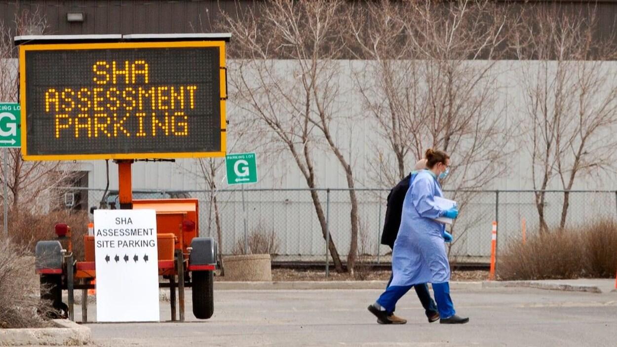 Un travailleur de la santé portant un équipement de protection individuelle accompagne un patient dans un centre d'évaluation de l'Autorité de la santé de la Saskatchewan.