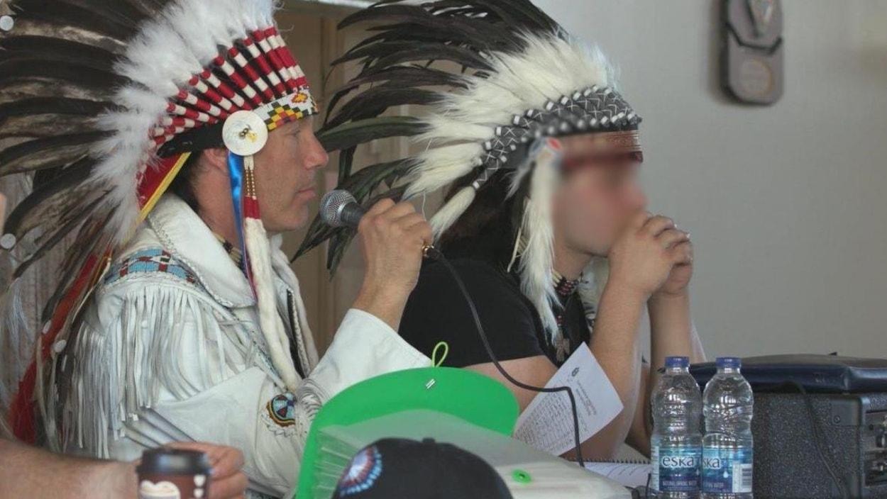 Guillaume Carle, portant un couvre-chef autochtone, parle au micro.