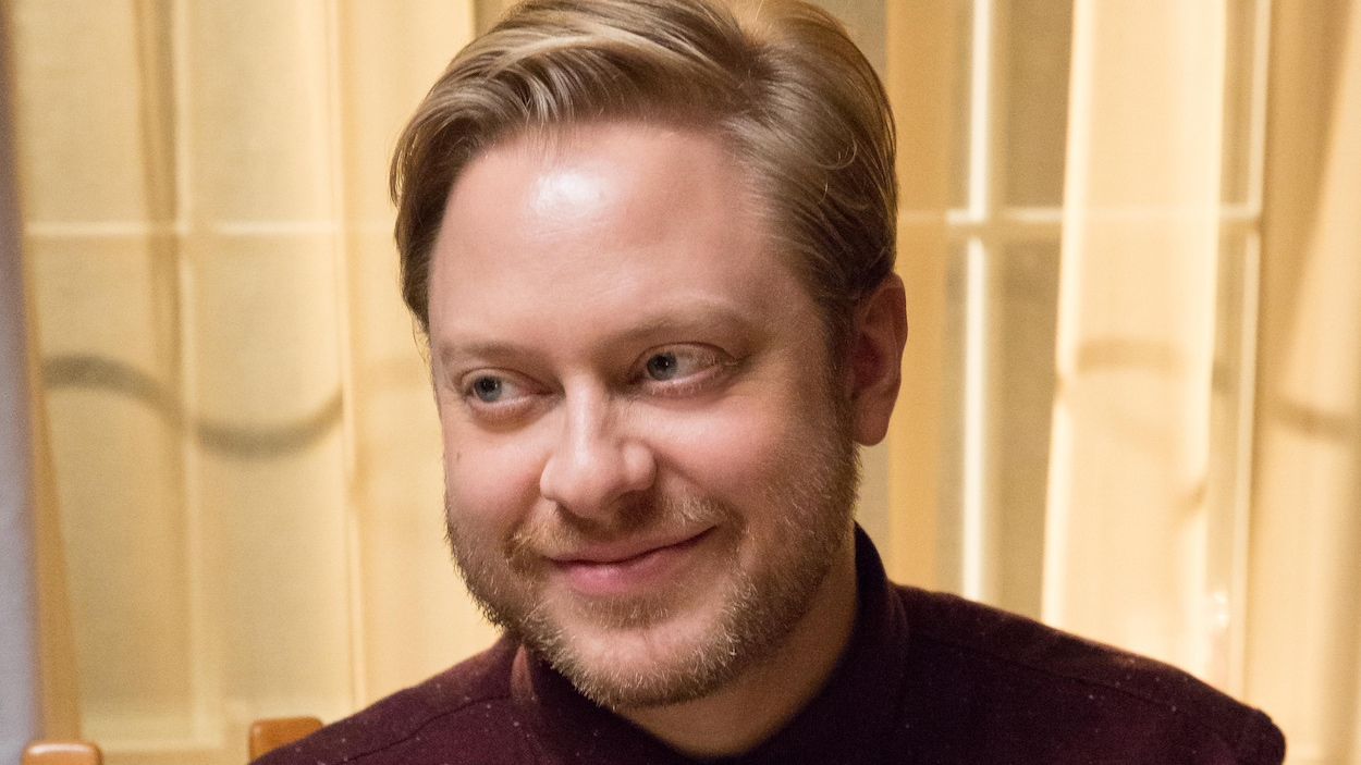 Guillaume Lambert, assis à une table lors d'un repas, dans une scène de la série « L'âge adulte ».