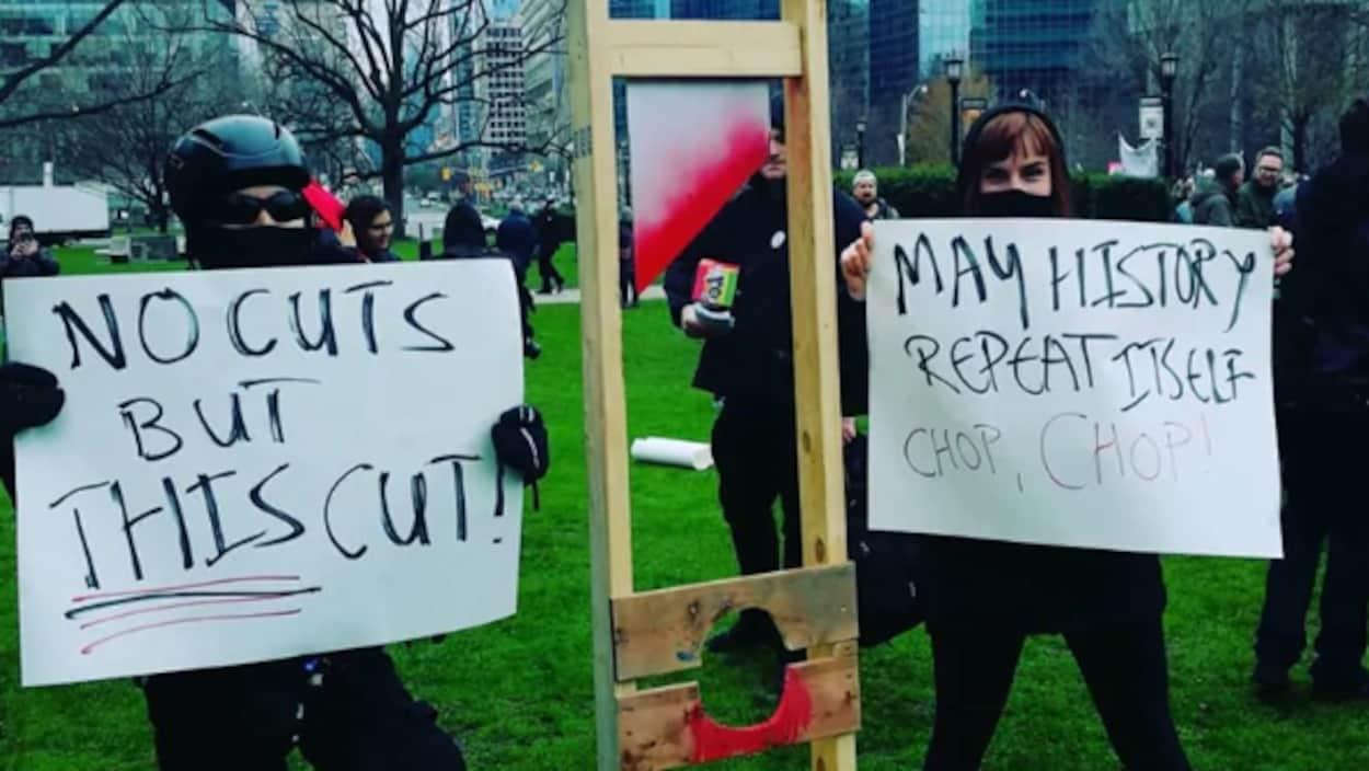 Des manifestants vêtus de noir et masqués tiennent des cartons où on peut lire des messages dénonçant les compressions.