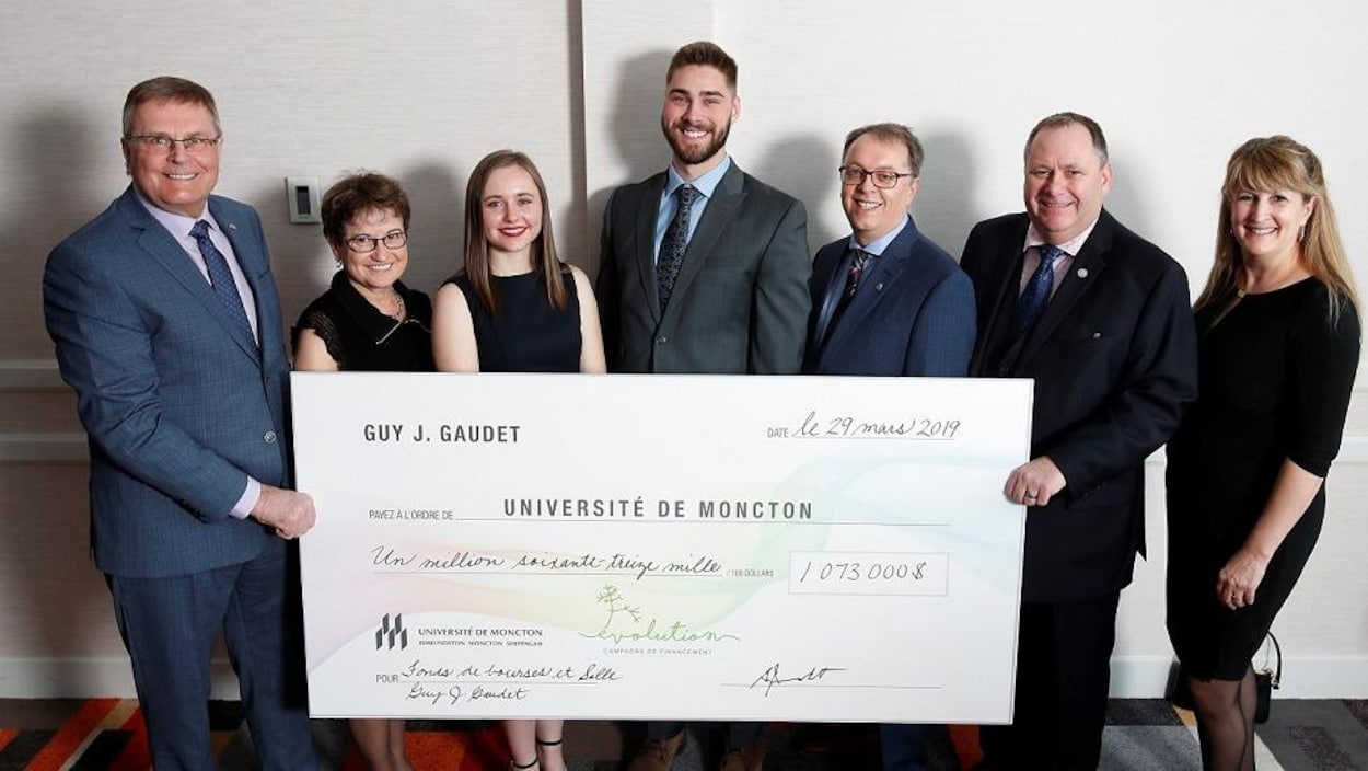 Guy J. Gaudet, grand donateur à la campagne de financement de l'Université de Moncton, présente un chèque grand format à divers intervenants.