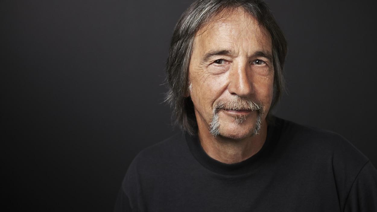 Portrait en couleur de Guy Lalancette sur fond gris foncé. Il regarde la caméra et esquisse un sourire. Il porte la moustache et les cheveux un peu longs.
