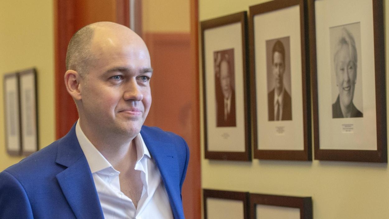 Guy Nantel passe devant des photos de leaders péquistes.