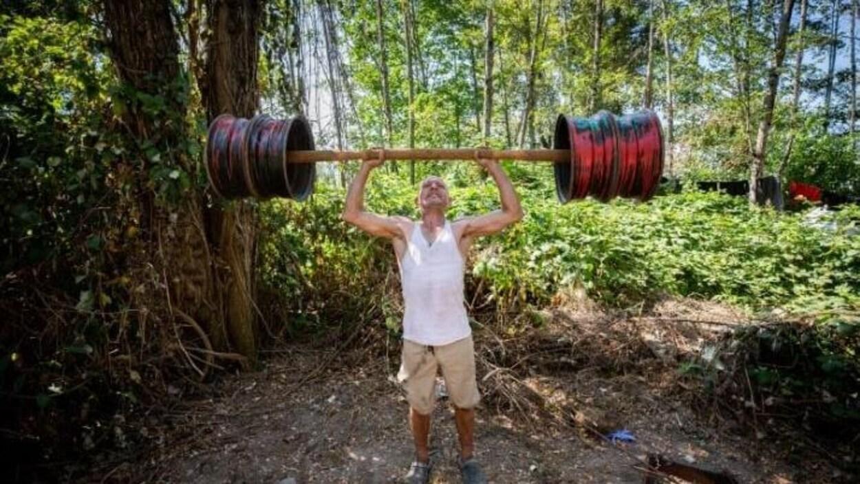 Un homme soulève des poids et haltères au milieu de la forêt.