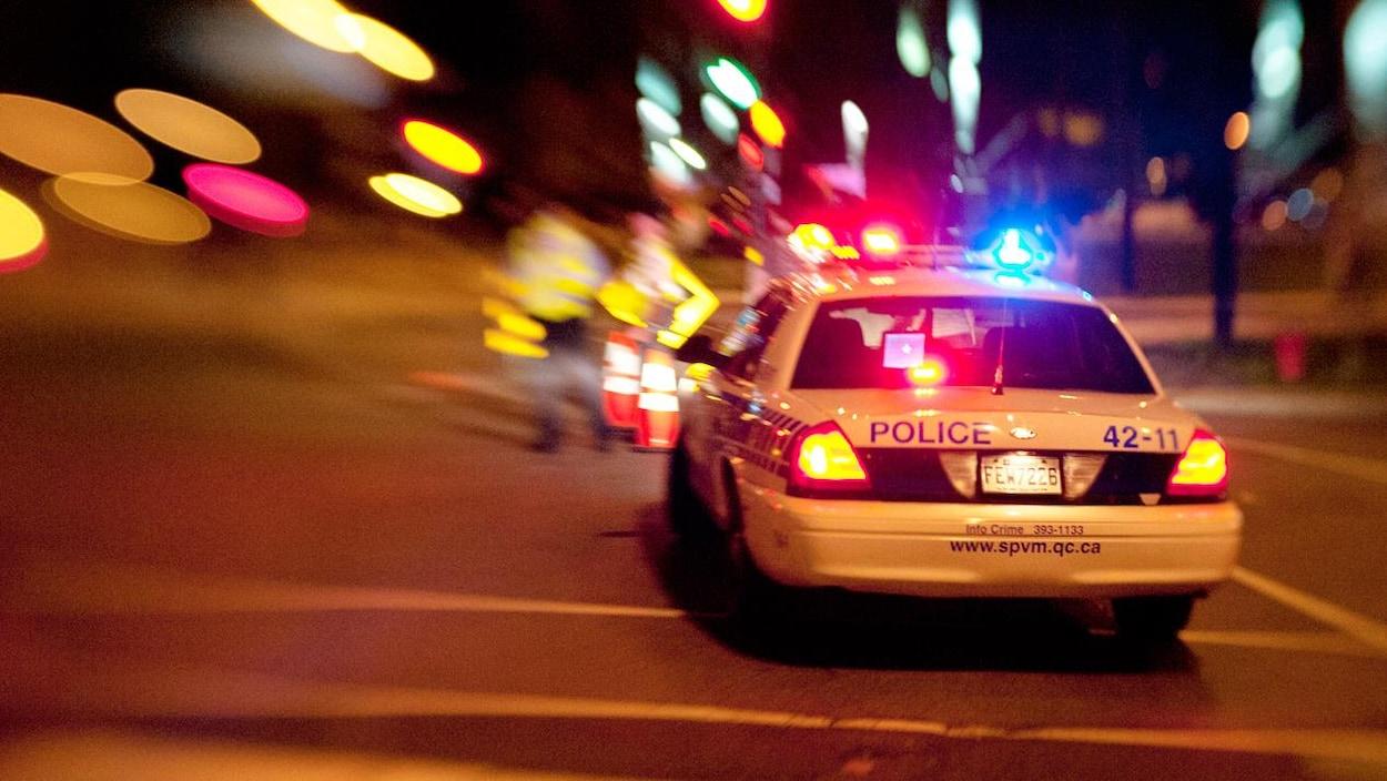 Zoom sur une auto-patrouille du Service de police de Montréal dans la nuit. Modèle désuet de Ford Crown Victoria.