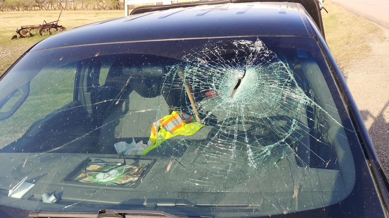 Vue de face d'un pare-brise brisé avec un trou longitudinal au niveau de la tête du conducteur. Un mache de hache est entre les sièges du conducteur et du passager.