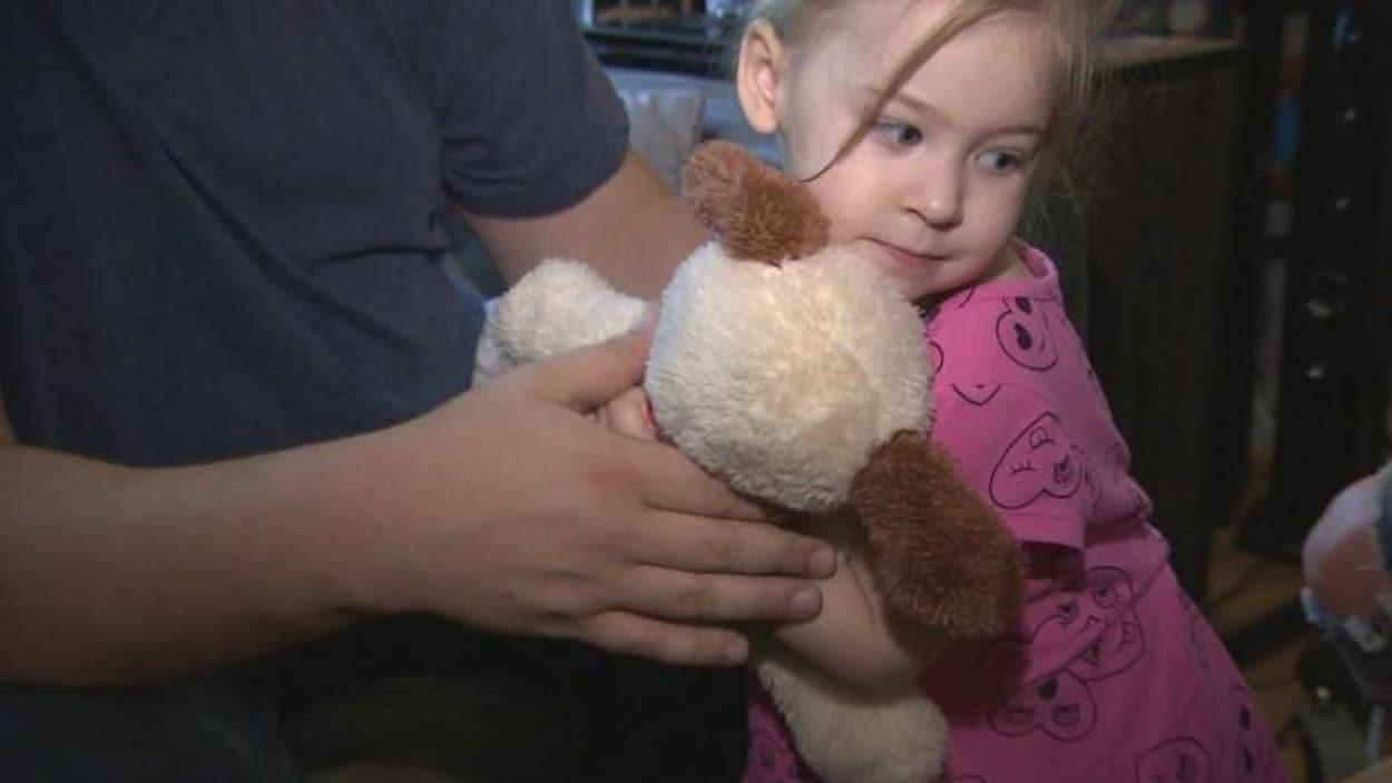 La petite fille tient son ourson dans les bras.