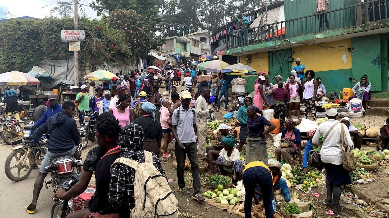 De nombreuses personnes s'affairent dans un marché public.