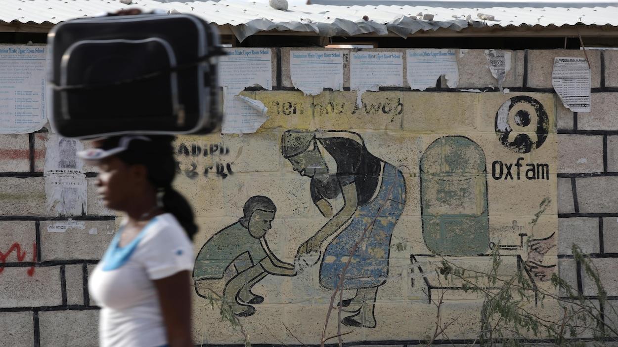 Une femme passe devant une publicité d'Oxfam en transportant une valise sur sa tête.