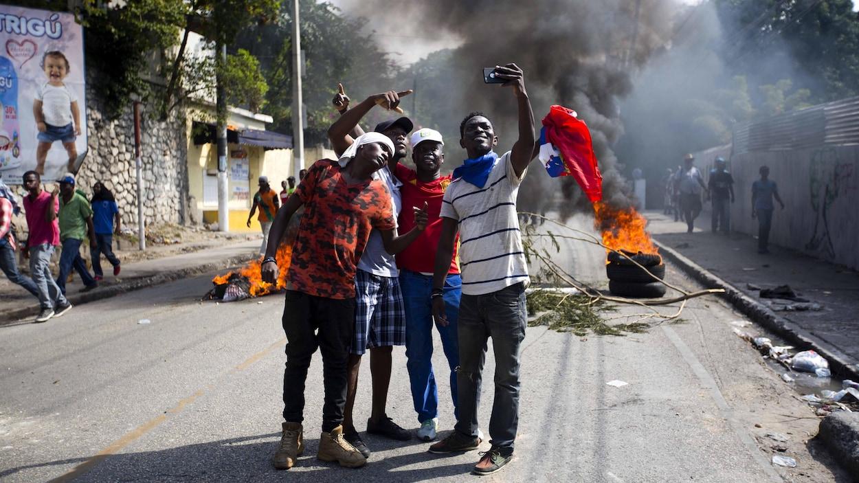 Quatre jeunes Haïtiens se prennent en photo avec un téléphone portable dans une rue où se déroule une manifestation avec des pneus en feu et une épaisse fumée.