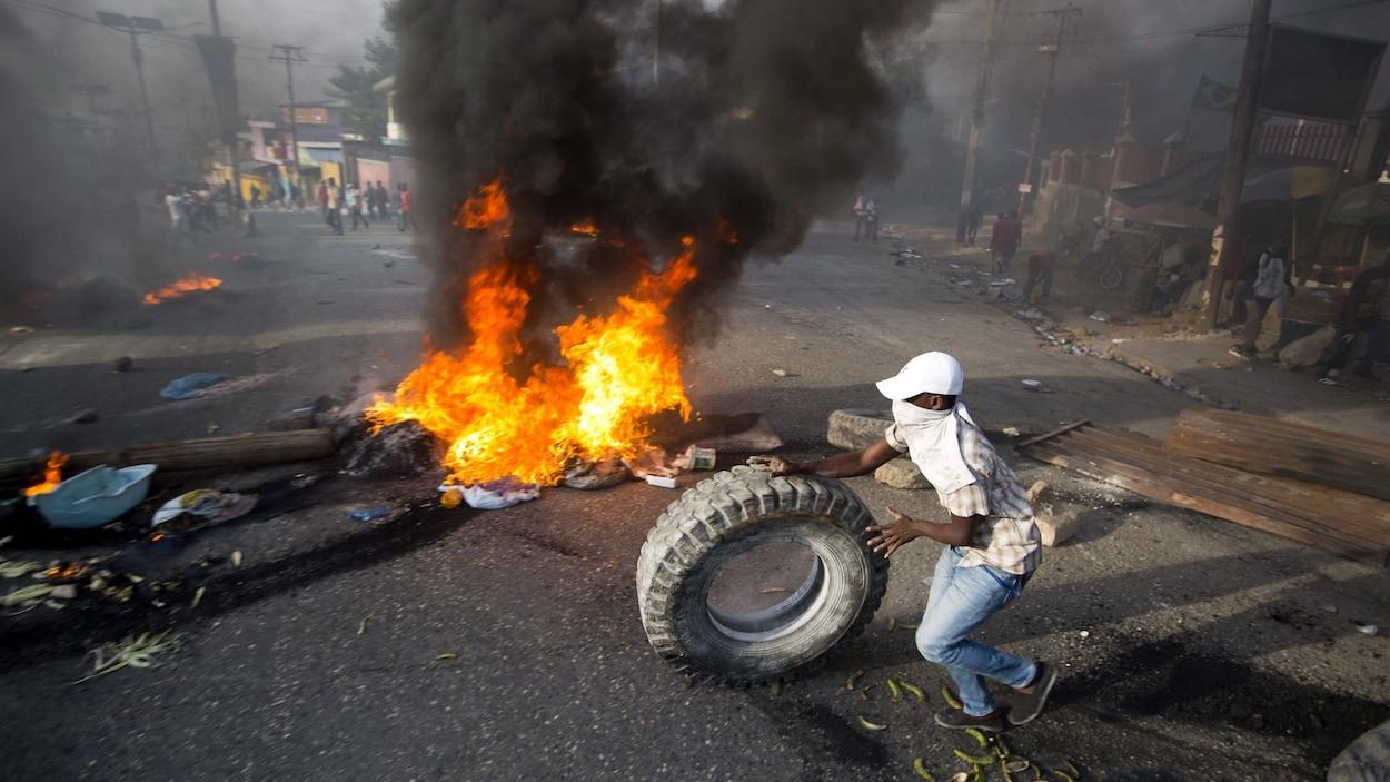 Un manifestant tenant un pneu devant un incendie en pleine rue.