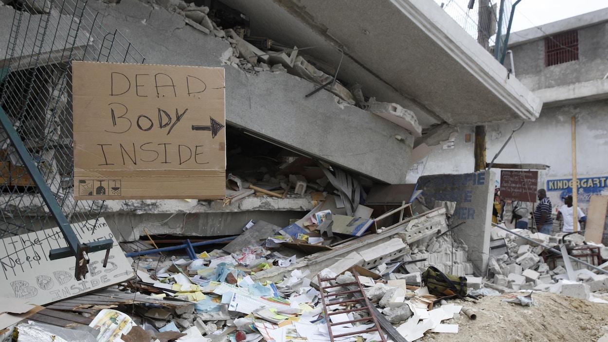 Une pancarte indique la présence de corps sous les décombres d'un immeuble effondré à Port-au-Prince, le 19 janvier 2010