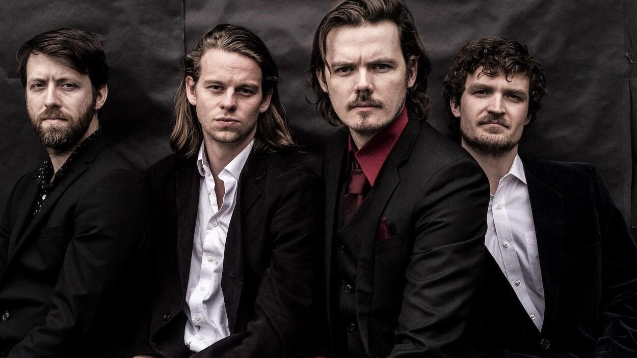 Les quatre membres du groupe Half Moon Run, portant des complets noirs et posant pour la caméra devant un fond noir.