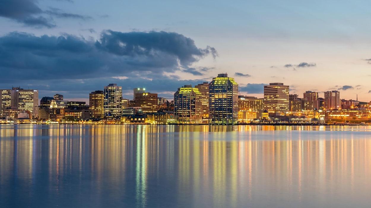 La lumière des édifices se reflète sur l'eau du havre au coucher du soleil en été.