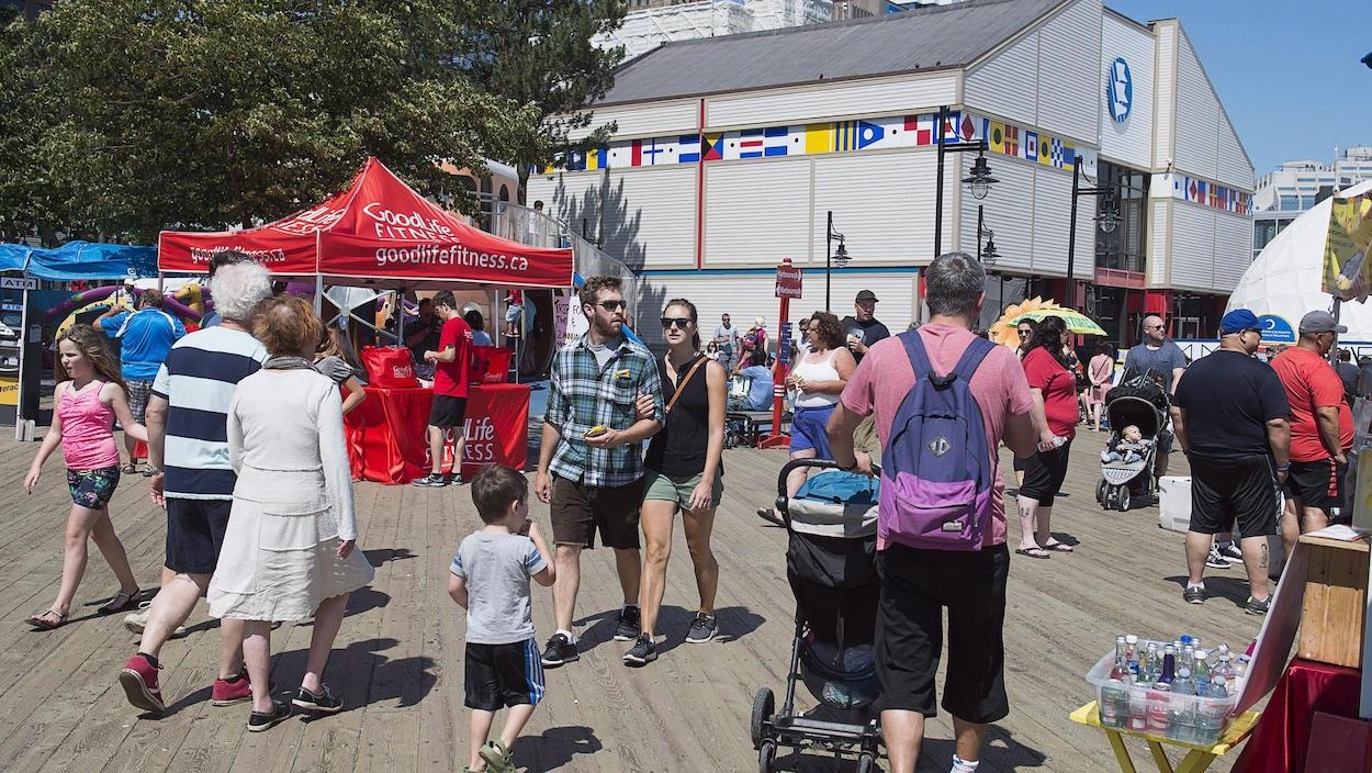Des adultes et des enfants se promènent sur le front de mer d'Halifax en été.