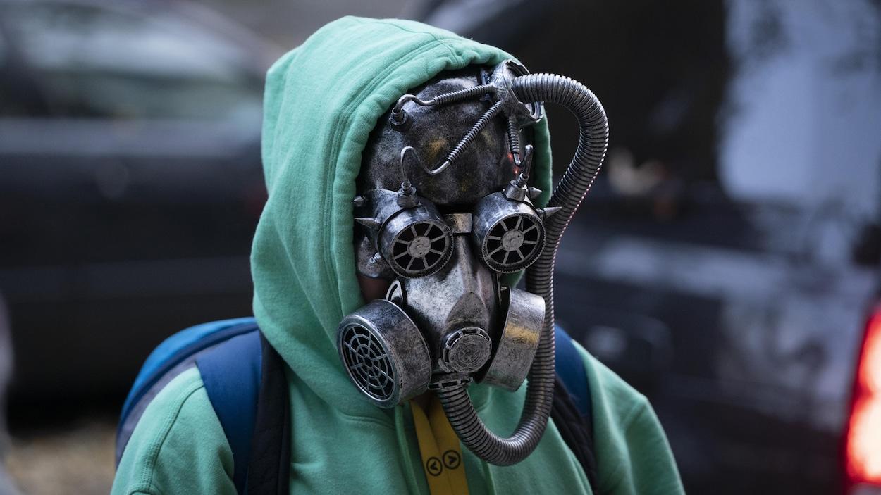 Un adolescent porte un masque à gaz peint en gris qui masque complètement sons visage et lui donne un air de fin du monde.
