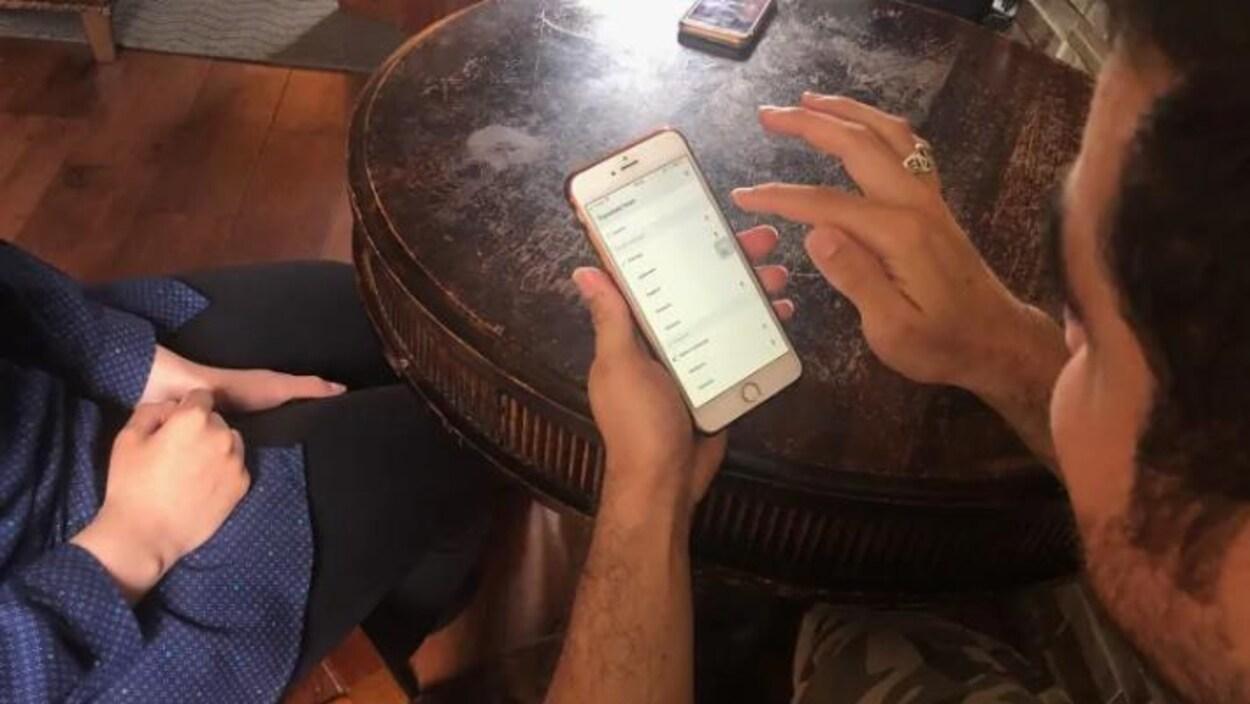 on voit les mains d'Hamid mais pas son visage, il a un cellulaire entre les mains et regarde l'application Google Traduction