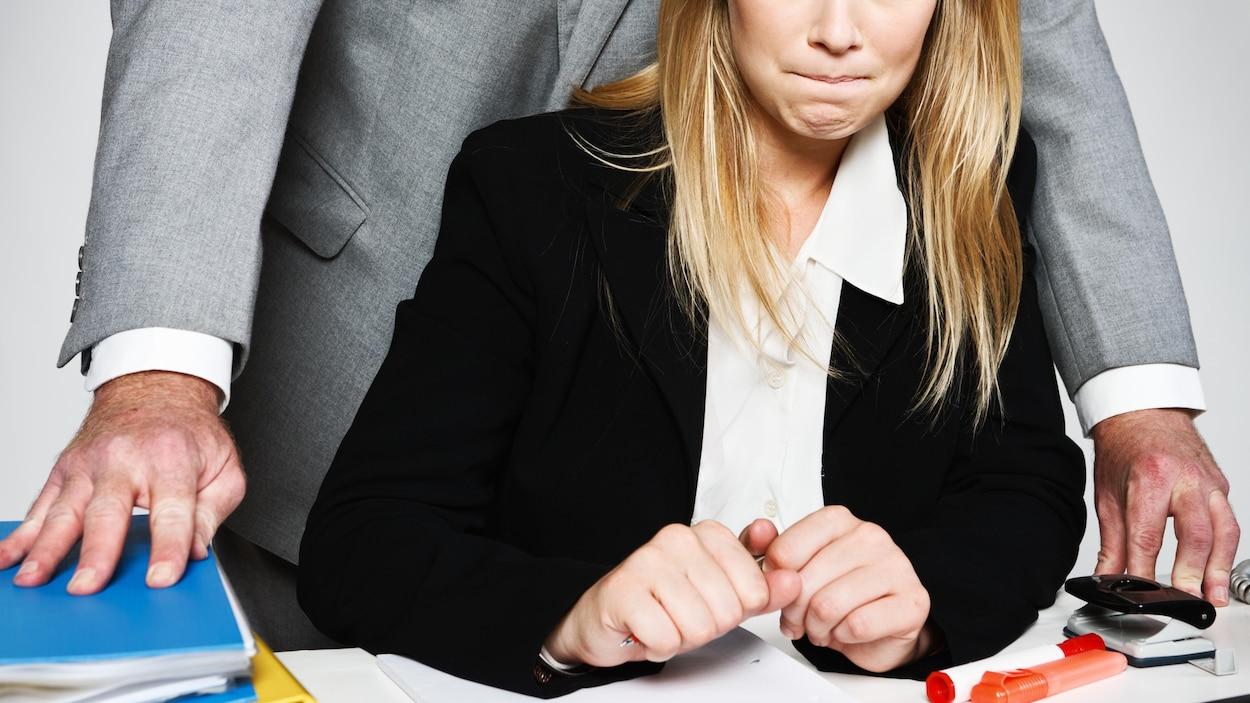Un homme se colle contre une femme assise à son bureau.