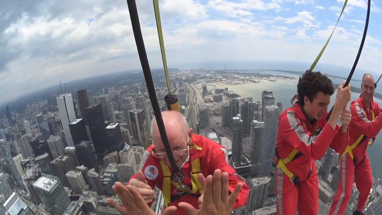 Harry Whalen tape dans les mains du guide de la Tour CN suspendu à 500 m de hauteur.