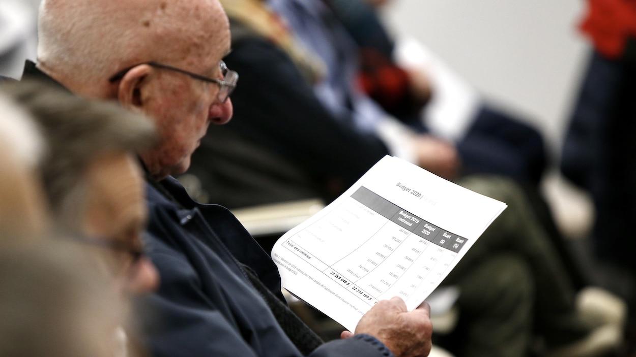 Un citoyen de L'Ancienne-Lorette regarde un document des faits saillant du budget municipal de 2020, le soir de son adoption, le 10 décembre 2019
