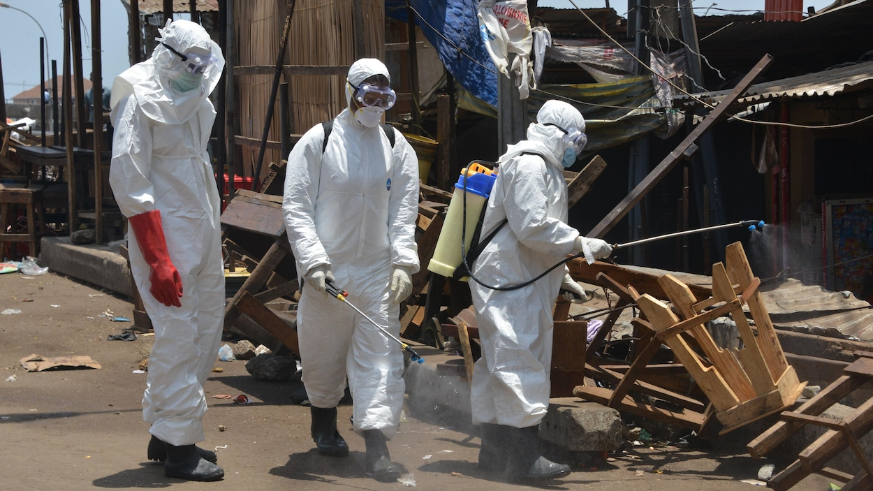 Trois personnes vêtues d'habits, de masques et de lunettes de protection désinfectent à l'aide de jets les rues et les habitations vétustes.