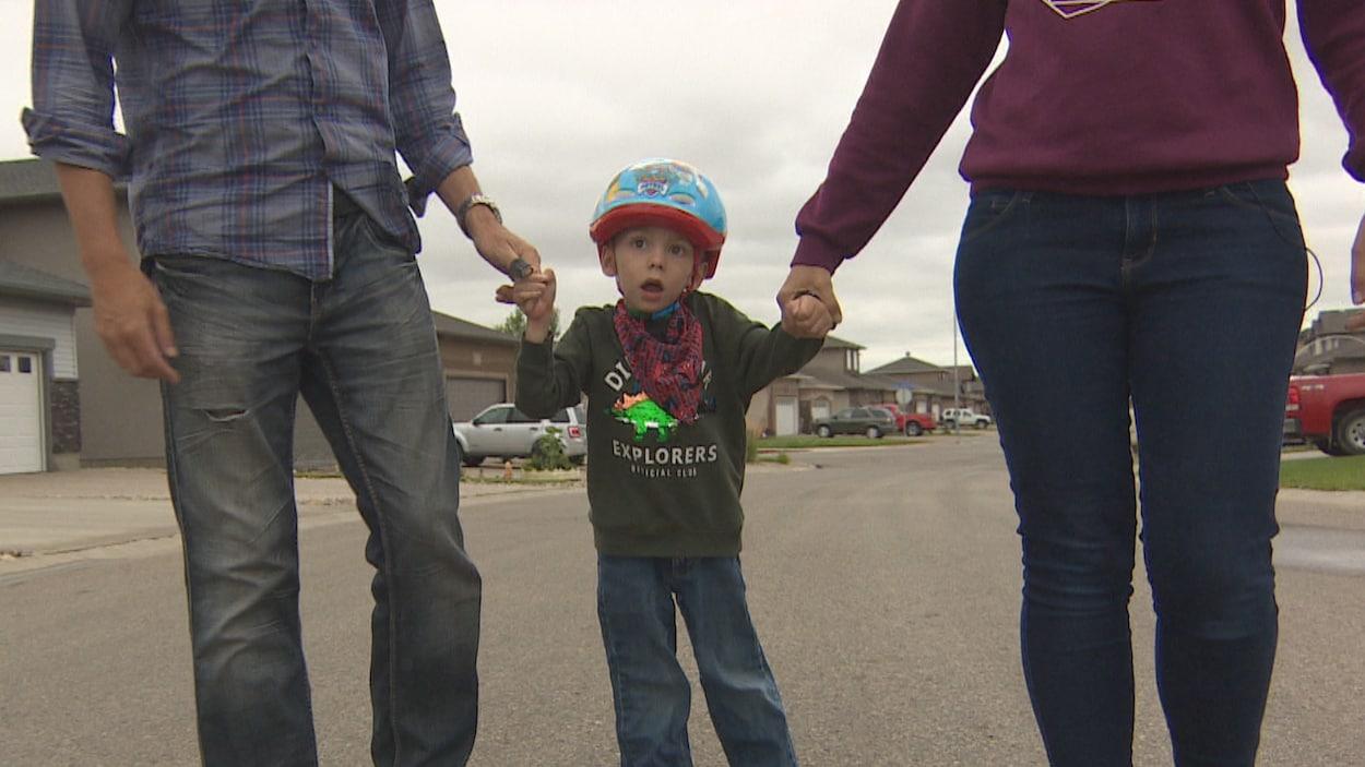 Un petit garçon avec un casque de vélo sur la tête marche dans une rue avec difficulté. Il tient la main de ses parents.