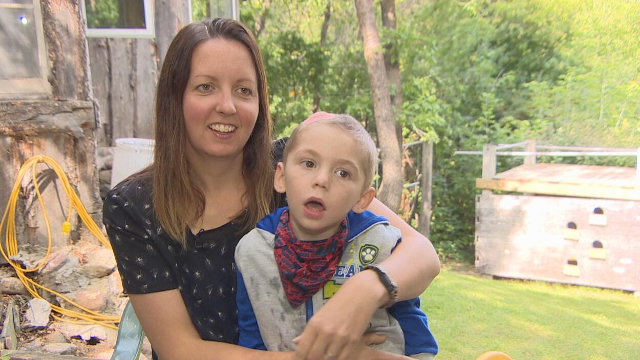 Une mère souriante tient un enfant de 4 ans dans ses bras. Il a un gros pansement sur le sommet du crâne.