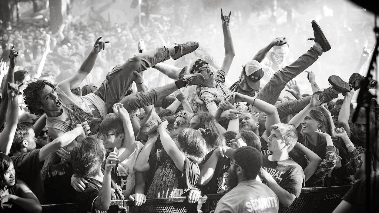 Des fans de métal surfent sur la foule au festival Heavy Montréal.