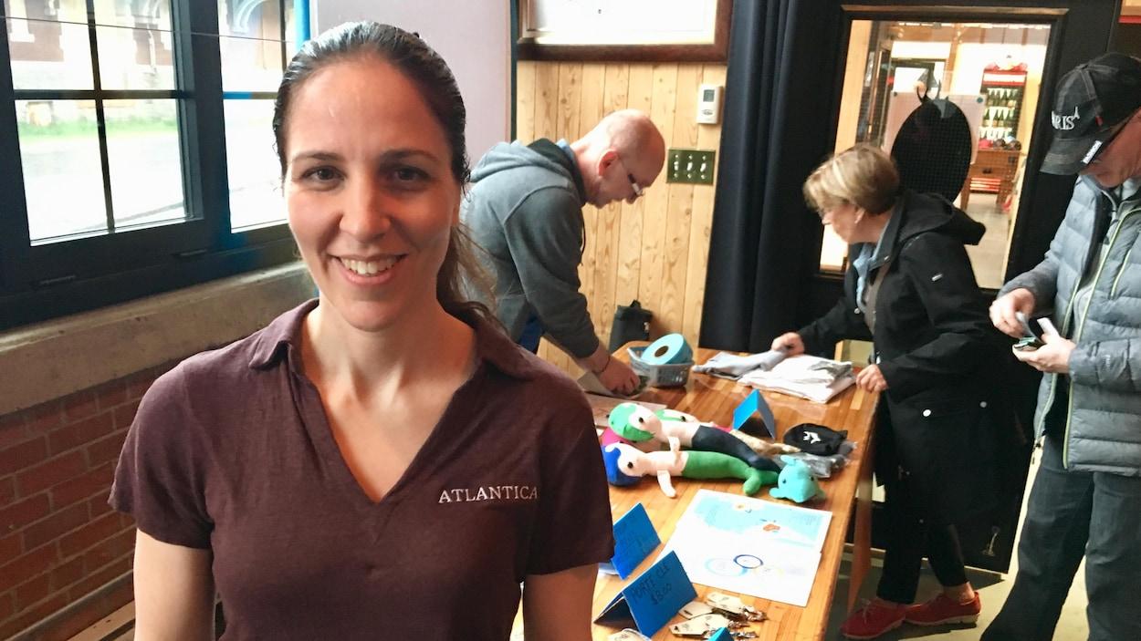 Heidi Levasseur devant la table où l'on vend des produits dérivés pour financer son projet Atlantica.