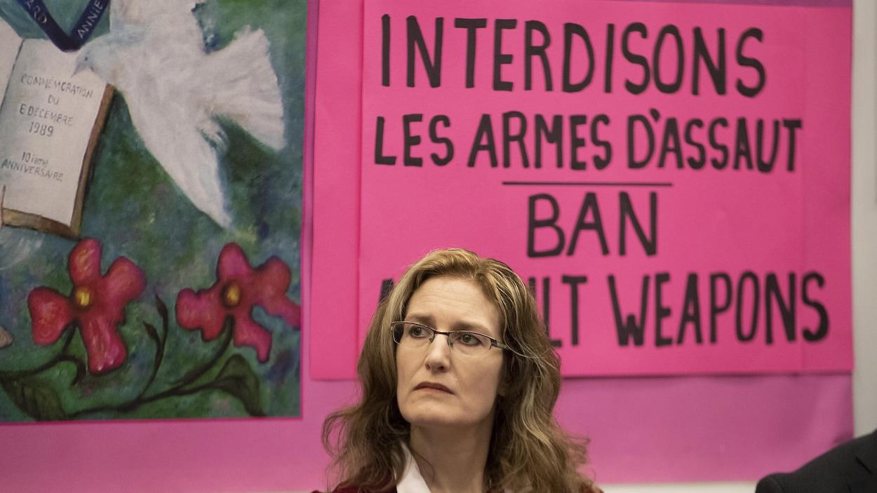 Heidi Rathjen devant une affiche appelant à l'interdiction des armes d'assaut.