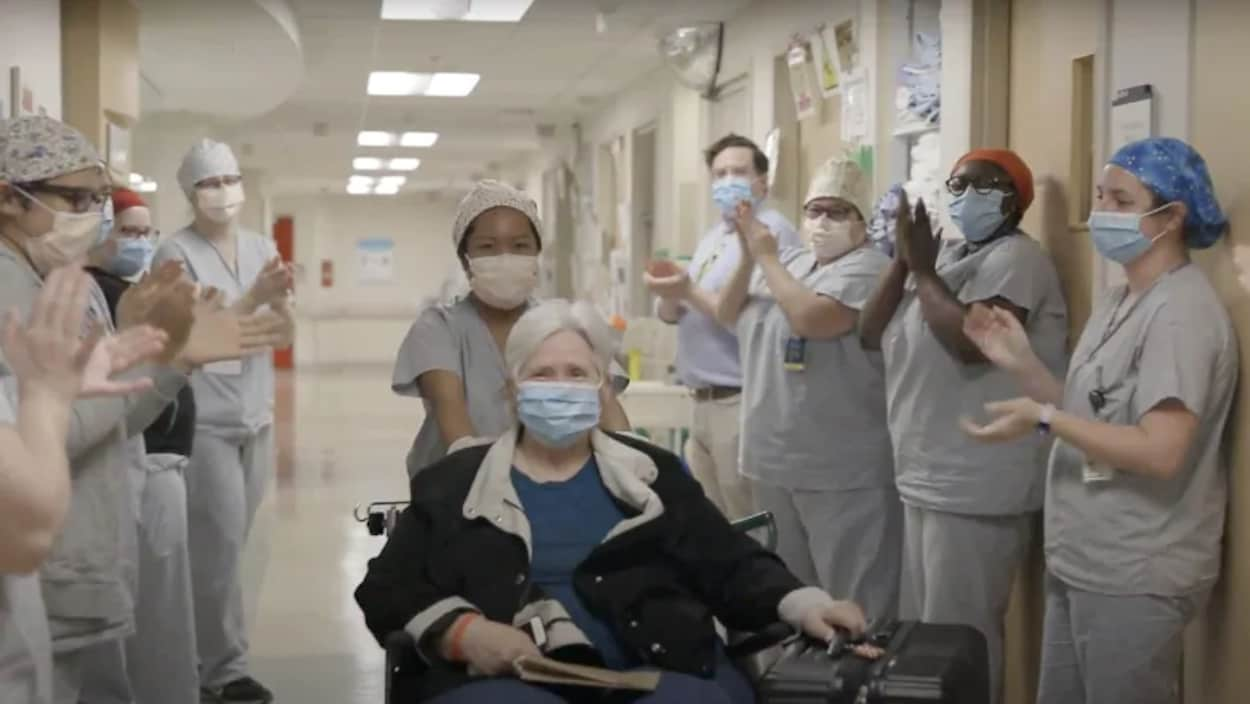 Helen Keene dans un fauteuil roulant sort de l'hôpital sous les applaudissements de travailleurs de la santé.