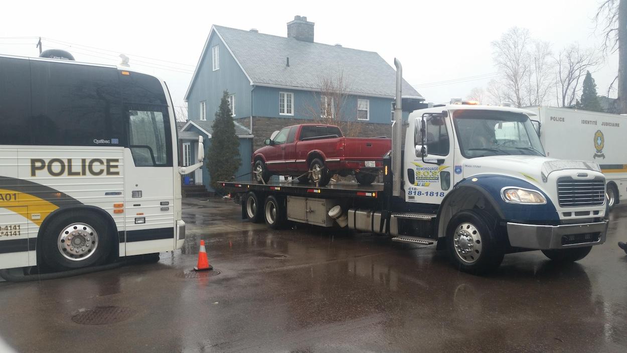 Camionnette sur la plateforme d'une remorque à la sortie d'une entrée résidentielle.