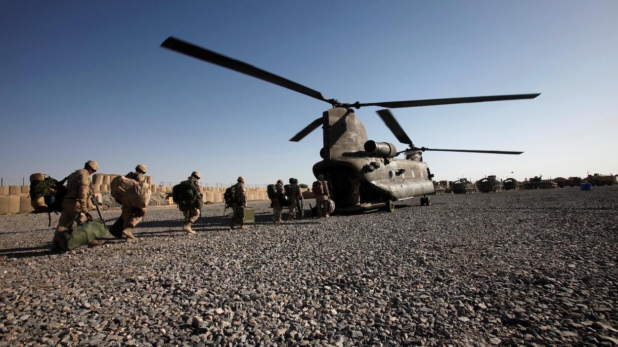 Des militaires canadiens s'apprêtent à quitter la base de Zangabad, en Afghanistan, à bord d'un hélicoptère de l'armée canadienne, le 18 juin 2011.