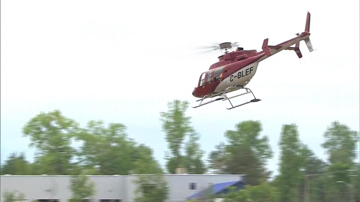 Un hélicoptère survole une bâtisse.