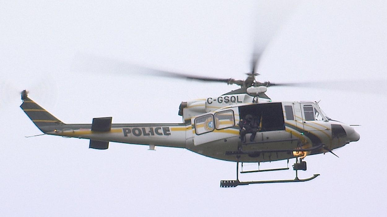 Un homme, assis sur le rebord d'un hélicoptère de la Sûreté du Québec, survole le secteur de Franquelin.