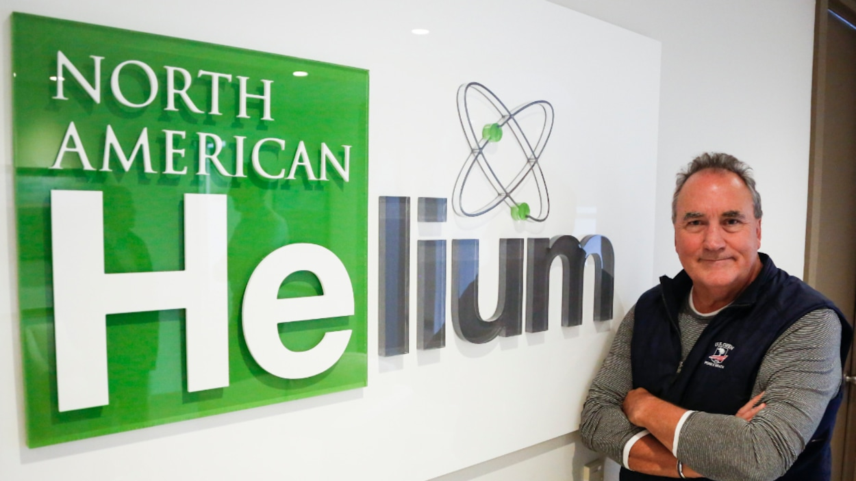Marlon McDougall pose pour le journaliste près du logo de sa compagnie.
