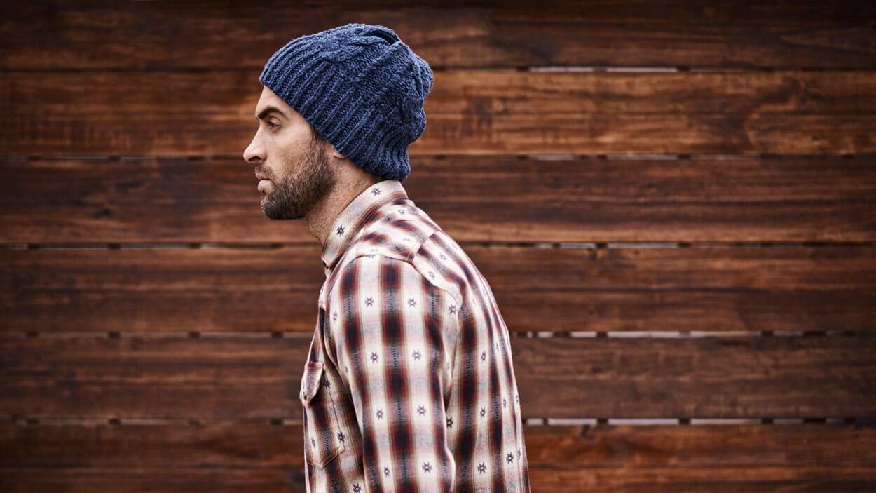 Un homme de profil avec une barbe portant une chemise et une tuque regarde devant lui.