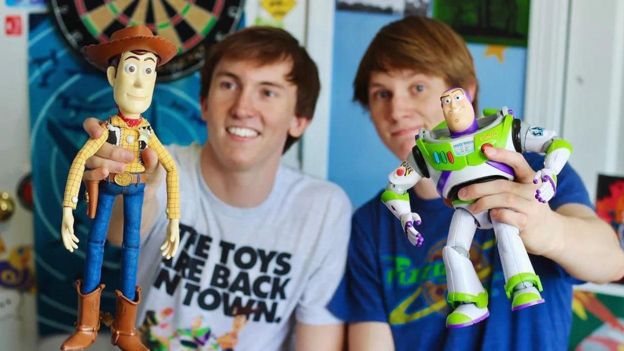 Deux jeunes hommes tiennent dans leurs mains des figurines de la série de films « Histoire de jouets ».