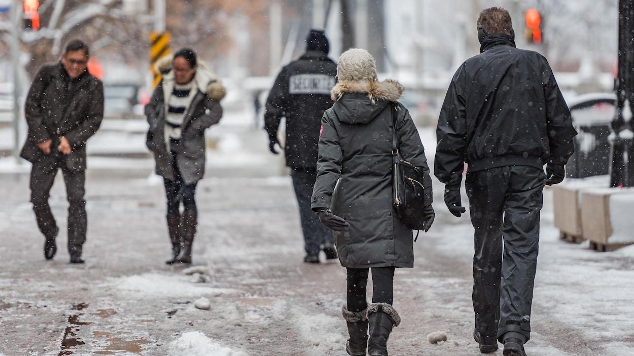 Des trottoirs enneigés à Ottawa, avec des piétons.