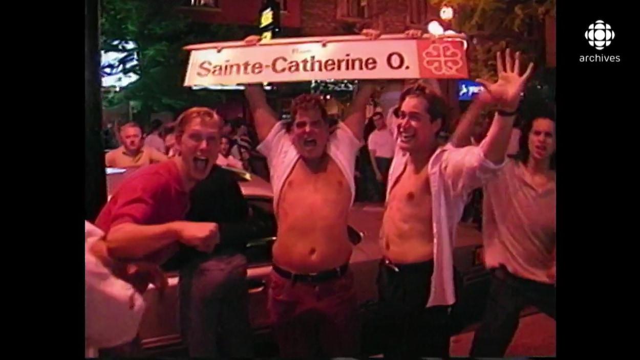 Trois hommes agités tiennent un panneau de signalisation routière de la rue Sainte-Catherine Ouest à Montréal.