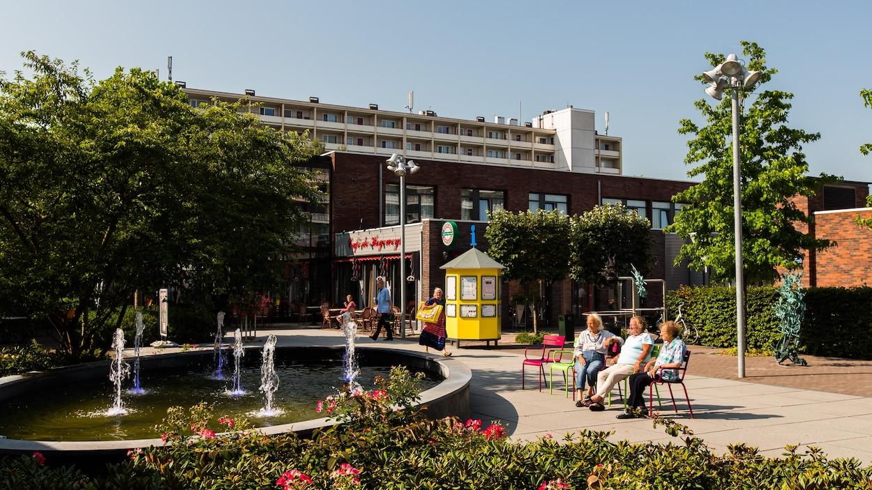 Des résidents sont assis sur des chaises au soleil devant une fontaine avec des immeubles en arrière-plan.